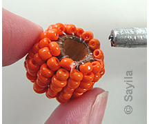 Decorate a large bead with seed beads